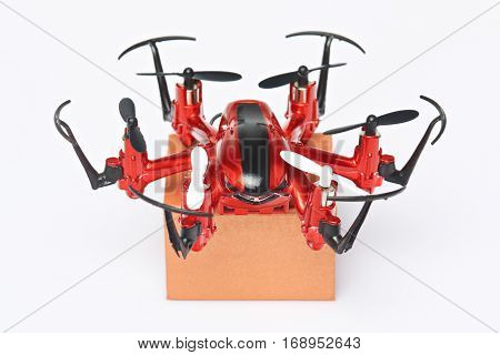 Closeup of drone with package box isolated on white background. Delivery of small boxes by air post