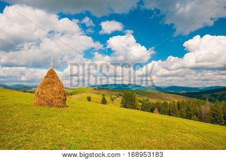 Haystack on a mountain meadow with blue sky and white clouds. Rural landscape in cloudy day. Carpathians, Ukraine, Europe