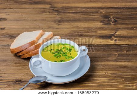 Chicken bouillon with fresh bread in the white bowl. Healthy and tasty food. Beautiful breakfest and dinner