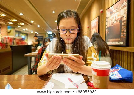 HONG KONG - CIRCA NOVEMBER, 2016: woman at Starbucks cafe in Hong Kong. Starbucks Corporation is an American coffee company and coffeehouse chain.