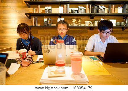 HONG KONG - CIRCA NOVEMBER, 2016: teenagers at a Starbucks cafe in Hong Kong. Starbucks Corporation is an American coffee company and coffeehouse chain.
