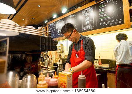 HONG KONG - CIRCA NOVEMBER, 2016: barista at a Starbucks cafe in Hong Kong. Starbucks Corporation is an American coffee company and coffeehouse chain.