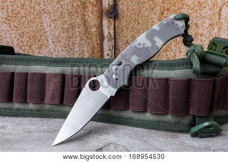 Folding knife on background bandolier. Knife with a knot.