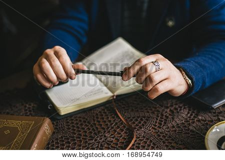 businessman sitting at a table and holding a pen over a notebook