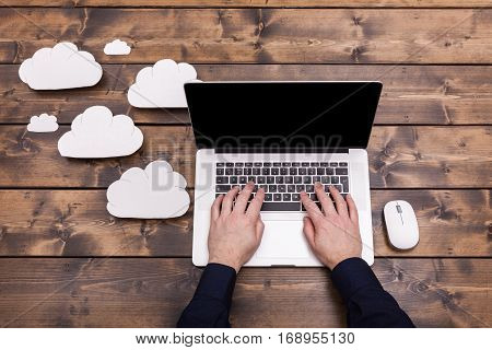 Cloud computing technology concept with white fluffy clouds next to the laptop. Mans hands typing the the keyboard uploading data on a wooden table.
