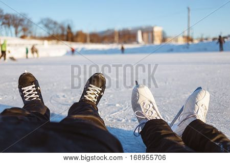 Male and Femal Feet in Ice Skates Lies On Ice Rink Surface. Concept Fun Winter Outdoor Sports.