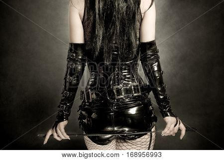 woman in black latex corset with horsewhip in hands