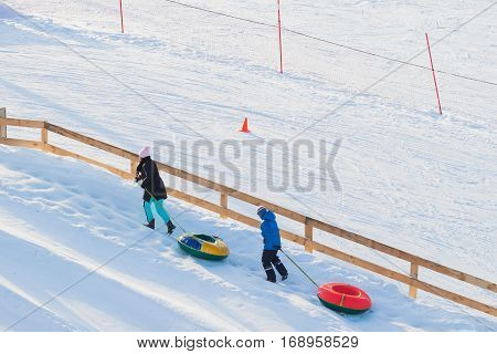 Children pulls toboggans on snowy slope at ski resort, winter leisure, active lifestyles, childhood, Christmas. Happy hobby, For background, place text