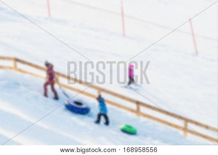 Children pulls toboggans on snowy slope at ski resort, winter leisure, active lifestyles, childhood, Christmas. Happy hobby