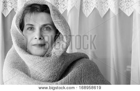 horizontal close up black and white image of a beautiful caucasian woman wearing a loosely wrapped head covering.