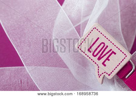 horizontal image of a white ribbon and pink paper background with a small pin with the word love on it with room for copy and text.