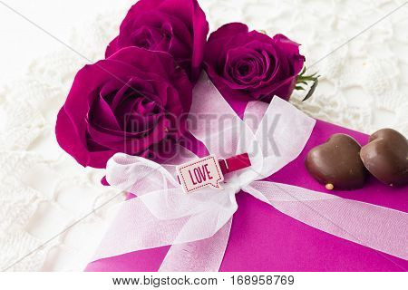 horizontal image of valentine scene of a part of a gift box wrapped in pink with white ribbon and three roses surrounding the box with two chocolates on white background