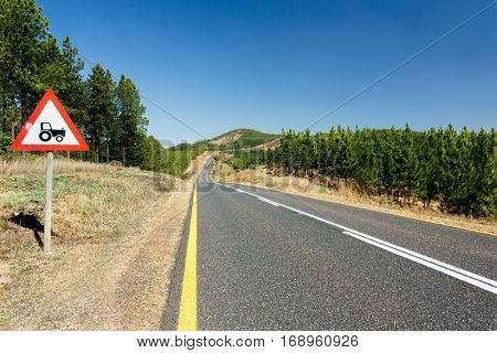 A tarmac countryside road with scenic views over rural hills and pine forest, near Graskop, South Africa