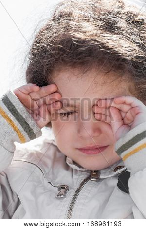 Close-up portrait of baby girl crying and covering her face outdoors
