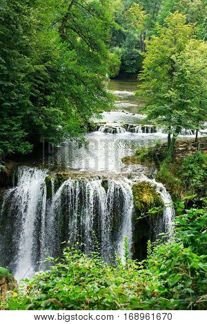 Beautiful forest cascade waterfall with clear healthy spring river water