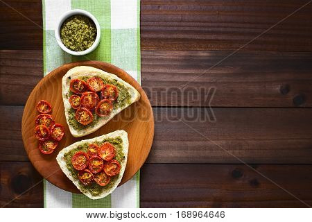 Olive bread roll halves spread with basil pesto and topped with roasted cherry tomato halves served on wooden plate photographed overhead on dark wood with natural light