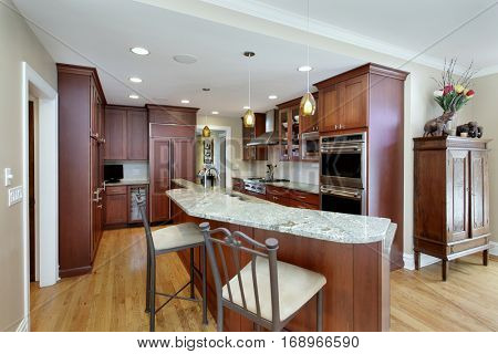 Modern kitchen with double decker island and cherry wood cabinetry.