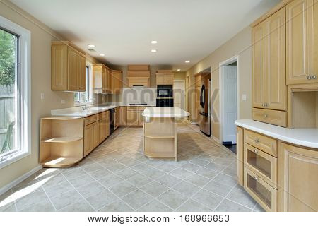 Kitchen in remodeled home with center island and oak wood cabinetry.