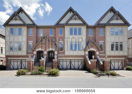 Row of tudor style brick townhouses with front gates.