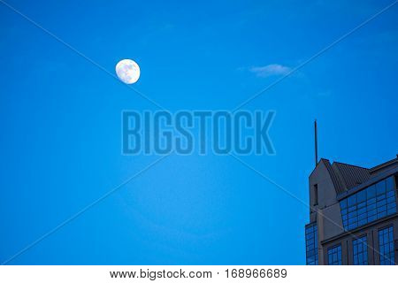 moon hovering over high rise building in the city