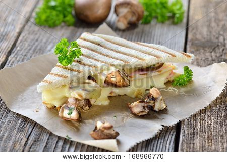 Pressed and toasted double panini with ham, cheese and mushrooms served on sandwich paper on a wooden table