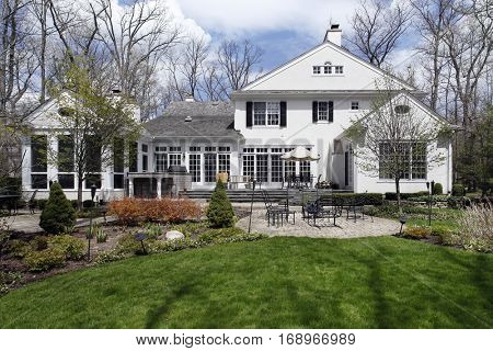 Rear view of upscale home with brick patio in early spring.