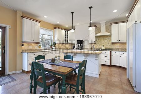 Kitchen in suburban home with eating area and green chairs.