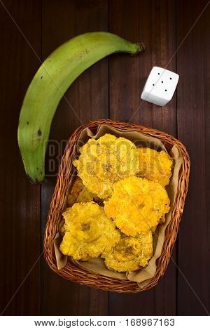 Patacon or toston fried and flattened pieces of green plantains a traditional snack or accompaniment in the Caribbean photographed overhead on dark wood with natural light