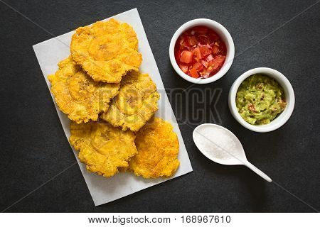 Patacon or toston fried and flattened pieces of green plantains a traditional snack or accompaniment in the Caribbean guacamole tomato and onion salad salt on the side photographed overhead on slate with natural light