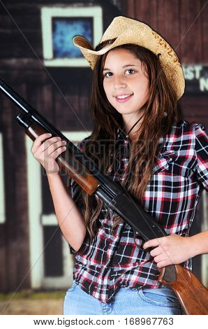 A pretty young teen cowgirl carrying her rifle near an old west building.