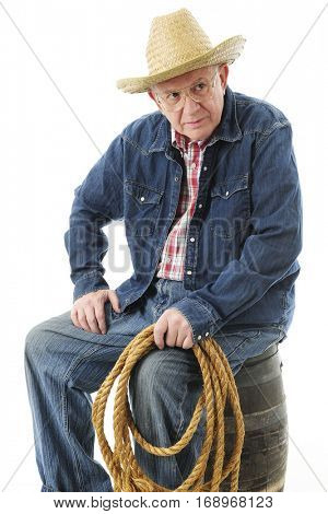 A senior adult cowboy appearing skeptical while sitting on an old barrel.  On a white background.