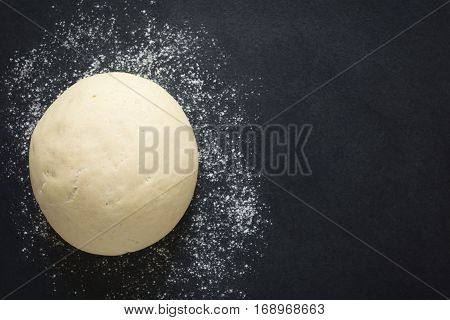 Risen or proved yeast dough for bread or pizza on a floured slate surface photographed overhead with natural light (Selective Focus Focus on the top of the dough)