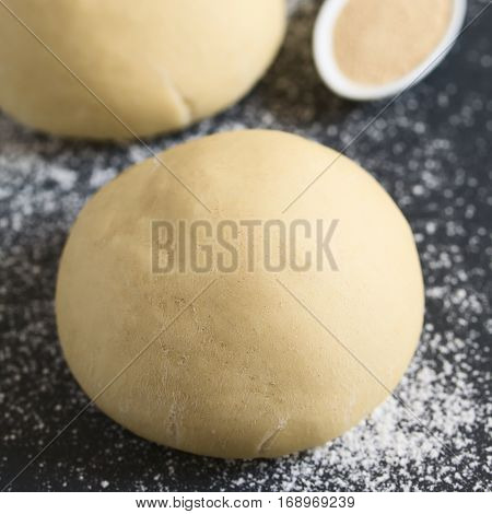 Risen or proved yeast dough balls for bread or pizza on a floured slate surface photographed with natural light (Selective Focus Focus on the front of the dough ball)