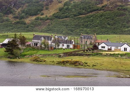 North Coast Scotland - June 6 2012: A handful of houses stand together along the Naver River on a green landscape with the of a rough brown and dark green mountain just behind them. Houses add whites and reds.