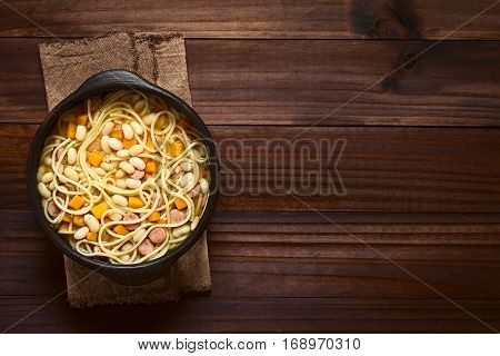 Chilean traditional Porotos con Riendas (beans with reins) dish of cooked dried beans with pumpkin onion spaghetti and sausage served in rustic bowl photographed overhead on dark wood with natural light