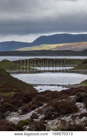 North Coast, Scotland - June 6, 2012: Irregularly shaped gray-water Loch Eriboll under dark cloudy skies. Wide shot showing land tongues background mountains and green and brown vegetation.