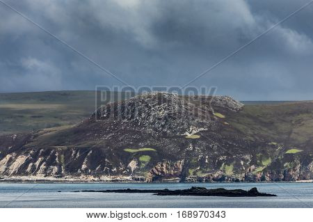 North Coast, Scotland - June 6, 2012: A huge dark brown boulder-hill along the shore of Loch Eriboll shows green and reddish patches under a dark gray sky. Small island peeps out of the bluish gray water.