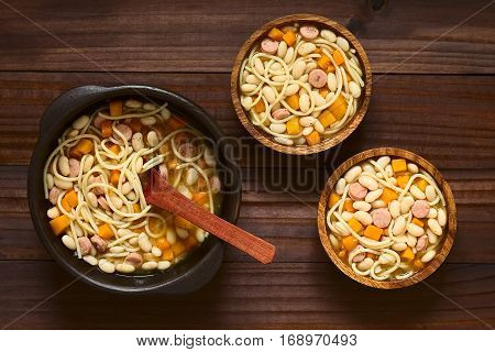Chilean traditional Porotos con Riendas (beans with reins) dish of cooked dried beans with pumpkin onion spaghetti and sausage in rustic bowls photographed overhead on dark wood with natural light