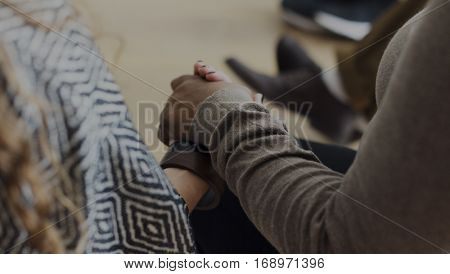 People in a counseling holding hands