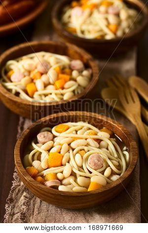 Chilean traditional Porotos con Riendas (beans with reins) dish of cooked dried beans with pumpkin onion spaghetti and sausage in wooden bowls photographed on dark wood with natural light (Selective Focus Focus in the middle of the first dish)