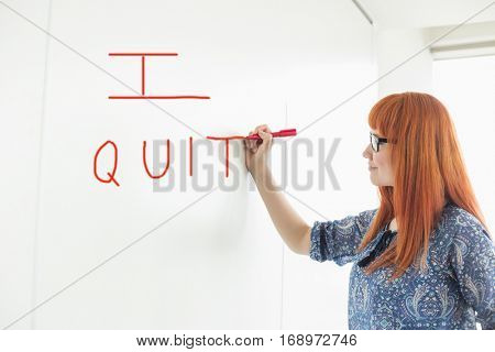 Smiling businesswomen writing on whiteboard in creative office with text saying I QUIT