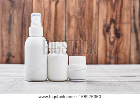 Remedy containers on wooden background. Small pill boxes. Forget about headache.