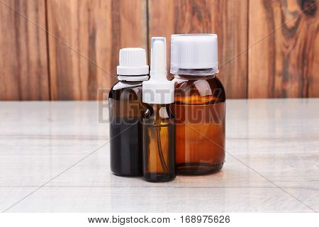 Remedy vials on wooden surface. Shelf with liquid medicine. How to stay healthy.