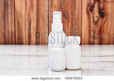 White remedy containers. Medical products on wooden backdrop.