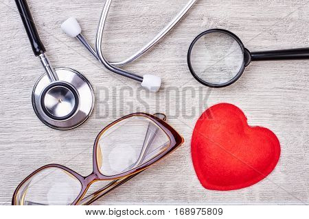 Stethoscope and glasses. Red fabric heart and loupe.