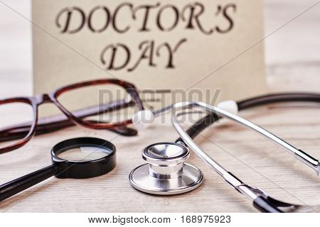 Loupe, stethoscope and greeting card. Spectacles on wooden surface.