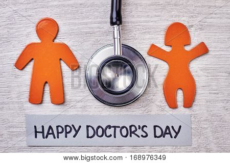 Stetoscope, stickmen on wooden surface. Happy Doctor's Day.