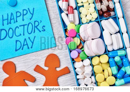 Pills, capsules in a box. Stickmen on a wooden backdrop. Celebration of Doctor's Day.