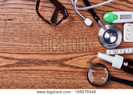Stethoscope, loupe, thermometer and pills. Medical tools and remedies. Say No to illness.