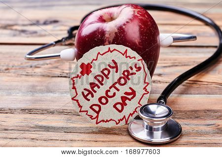 Apple, Doctor's Day card, stethoscope. Medical national holiday.